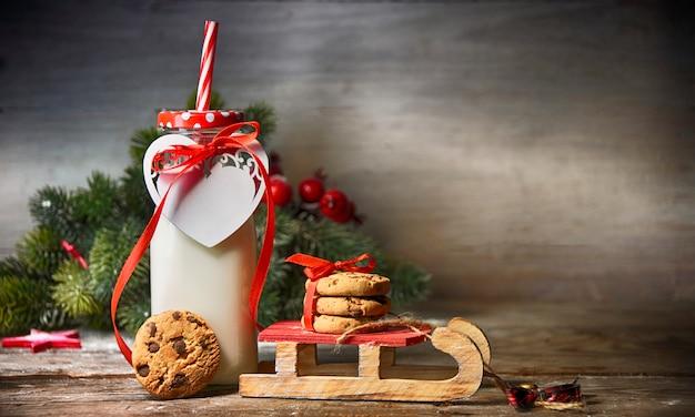 素朴なクリスマスの背景にミルク、クッキー、サンタ