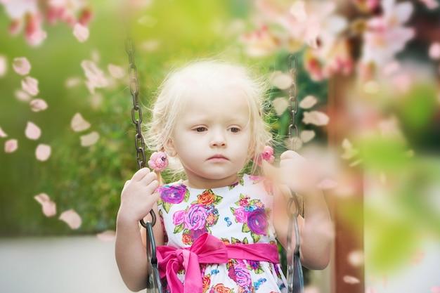 Очаровательная маленькая девочка развлекается на качелях