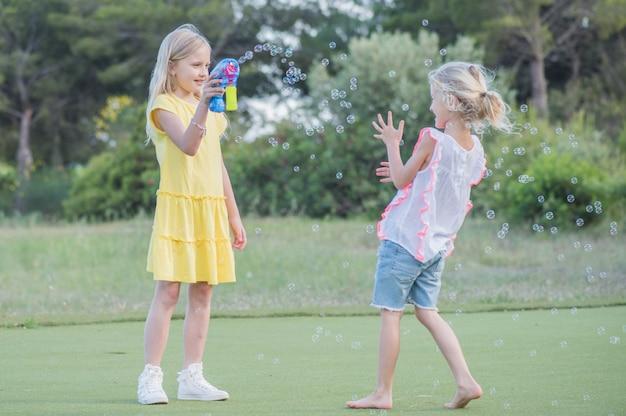 屋外でシャボン玉を吹く二人のかわいい女の子、夏の楽しみ。