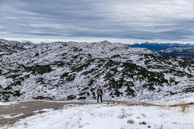 若い女性は山の景色を楽しんでいます