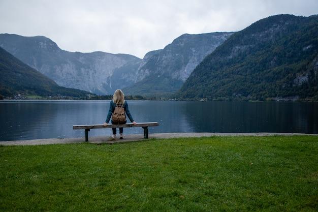 山の湖のそばのベンチに若い女性が景色を楽しんでいます