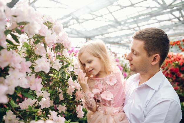 Отец держит дочь в цветущем саду