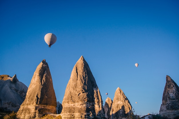 Воздушные шары летят над острыми камнями в каппадокии