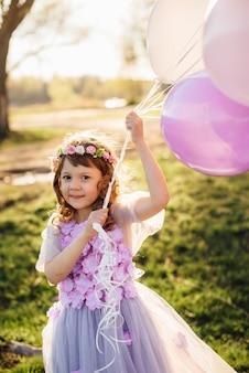 公園で風船で遊ぶ美しい紫色のドレスの女の子