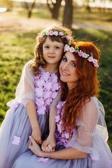 Молодая рыжая мать с дочерью отдыхает на природе на солнце