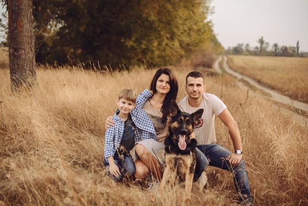 彼らの犬と一緒に芝生の上に座っているママのお父さんと息子
