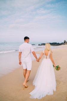 Молодожены гуляют по тропическому пляжу, вид сзади