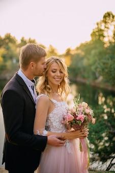 夕日に立って幸せな新婚夫婦