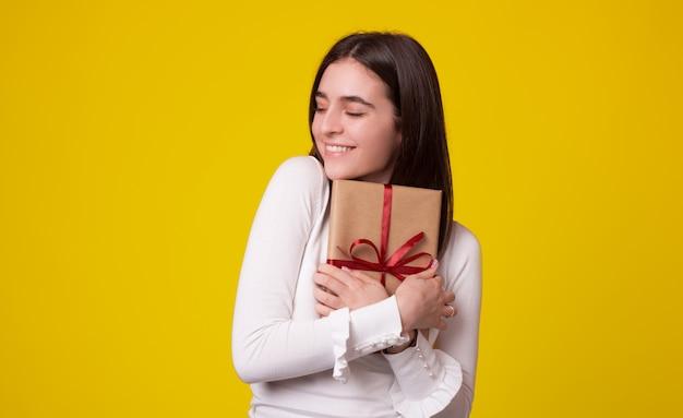 Милая девушка обнимает упакованный подарок на желтом фоне.