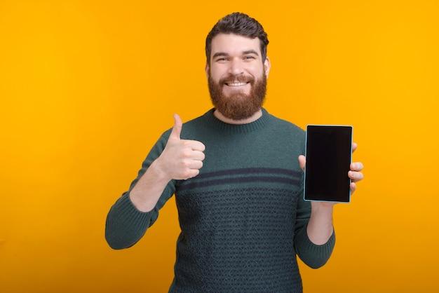 Улыбающийся человек показывает палец вверх и его таблетка пустой экран.