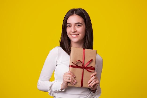 かわいい笑顔の女の子は黄色の背景に包まれたギフトを持っています。