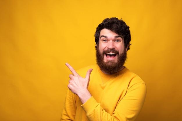 笑みを浮かべて男は彼の後ろの黄色の背景を指しています。