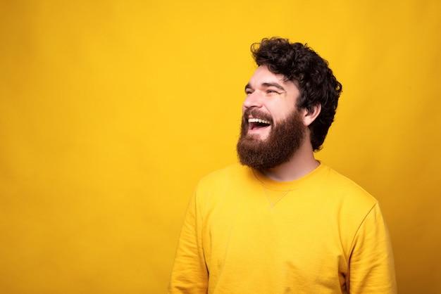 黄色の背景に大きな笑顔でうれしそうな男のシンプルな肖像画。