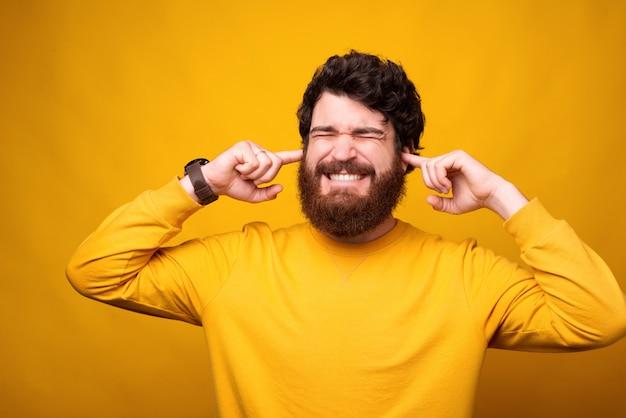 Я не хочу это слышать. бородатый мужчина закрывает уши пальцами.