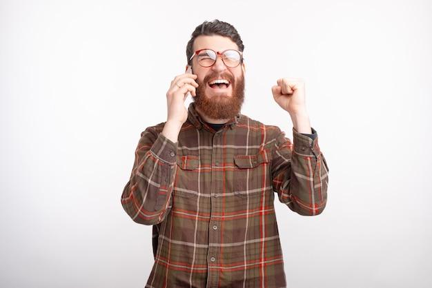Бородатый мужчина разговаривает по телефону, слышит хорошие новости, делает жест победителя.