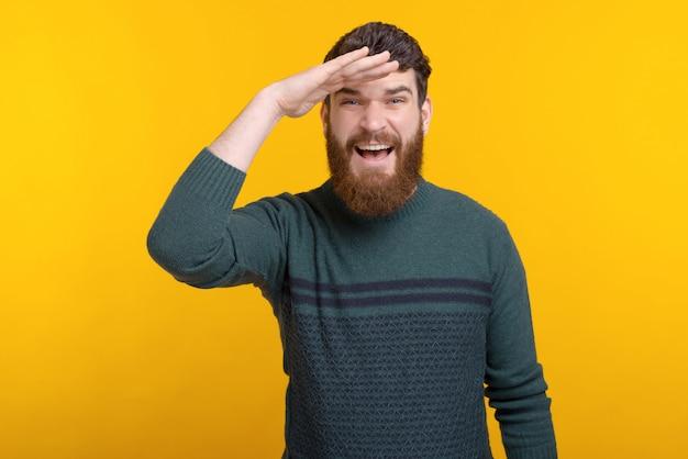 Портрет бородатого мужчины, глядя вперед, стоя над желтой стеной