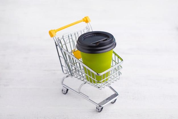 行く、オンラインショッピングの概念のコーヒーカップと黄色のトロリー