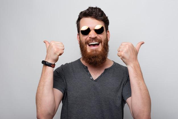 Веселый и улыбающийся молодой человек с бородой носить солнцезащитные очки и показывает палец вверх, успех и победитель концепции