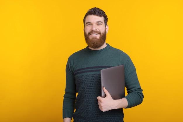 Портрет красивый молодой человек улыбается и держит ноутбук