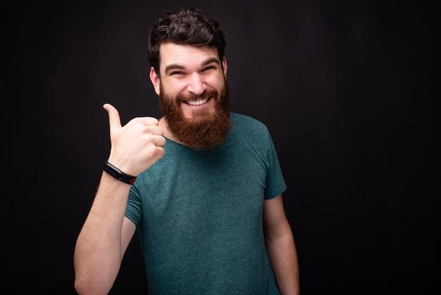 Улыбающийся возбужденный бородатый человек показывает палец вверх