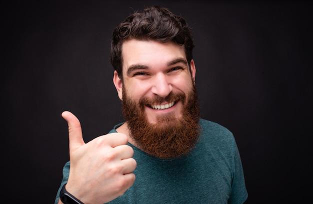 Крупным планом портрет улыбающегося бородатого мужчины битник показывает палец вверх стоя на черном фоне