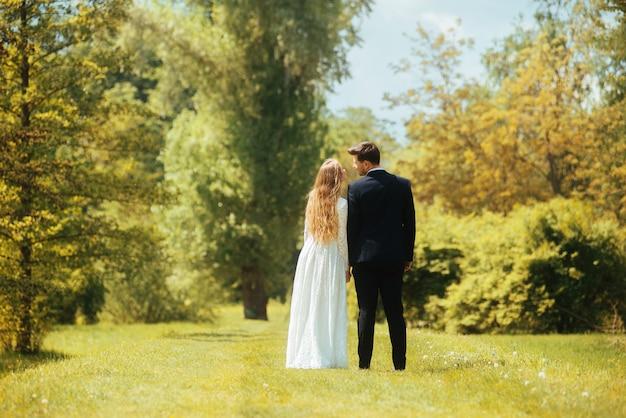 Заднее фото невесты и жениха, взявшись за руки и глядя друг на друга открытый в парке или лесу.