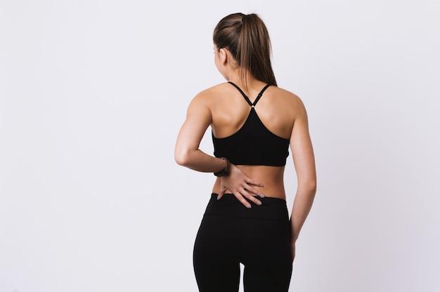 Молодая женщина фитнеса чувствуя боль в спине стоя над белой стеной