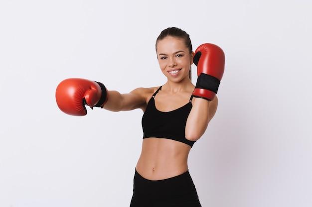 Портрет молодой жизнерадостной женщины фитнеса с перчатками красной коробки