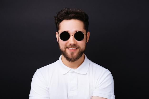 ハンサムなひげを生やした若い男が黒の背景を楽しみにヴィンテージの丸い黒い眼鏡をかけています。