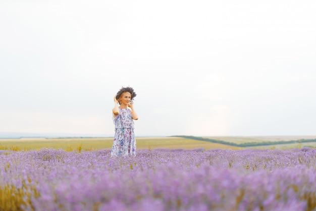 ラベンダー畑にラベンダーローレル立って身に着けている若いブロンドの女性。フェミニンなコンセプト。