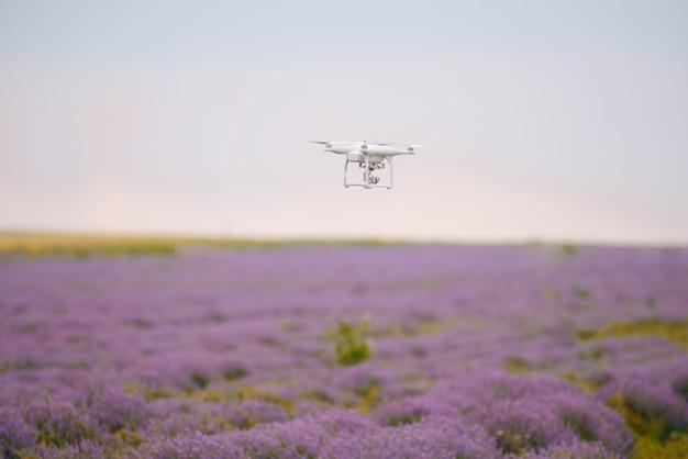 ラベンダー畑の上を飛んでいるドローンの写真。