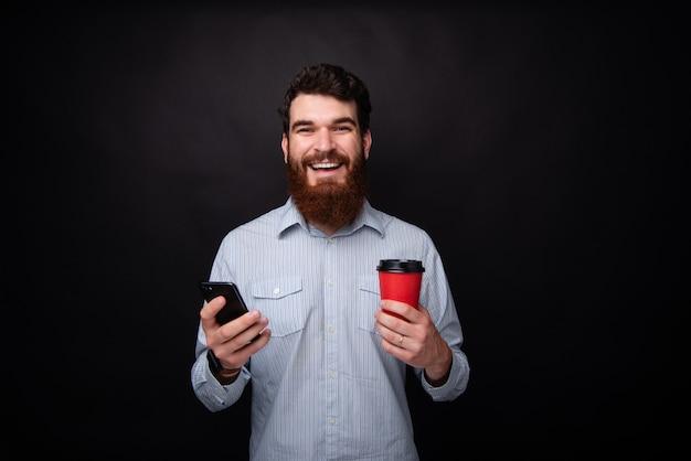 ひげを生やした男の写真。孤立した暗い背景の上にスマートフォンと一杯のコーヒーを押しながらカメラを見て