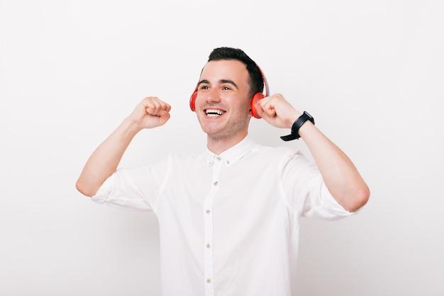 うれしそうな若い男は頭にヘッドフォンで幸せな人の叫びと白い背景の上のスタジオで音楽を聴きます。