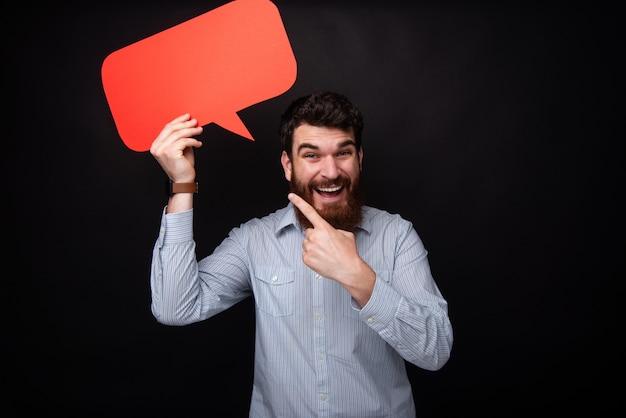 Фото красивый бородатый мужчина, проведение пустой пузырь речи, глядя на камеру, указывая на красный пробел