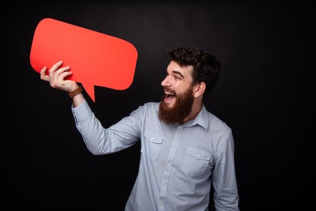 Фотография бородатого мужчины, весело держащего речь красного пузыря и смотрящего на него, стоящего на темно-сером фоне