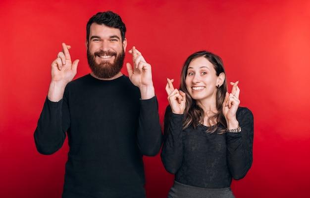 Портрет красивая пара мечтает со скрещенными пальцами