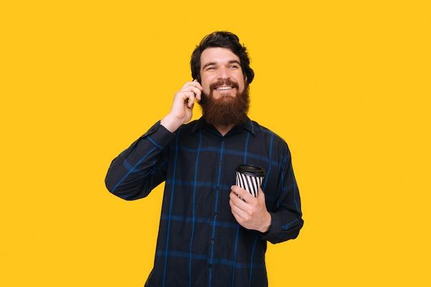 Бородатый мужчина разговаривает по телефону над желтой стеной, держа чашку с кофе