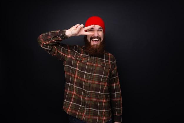 Портрет бородатого мужчины, делающего знак темпа перед глазом по темной стене