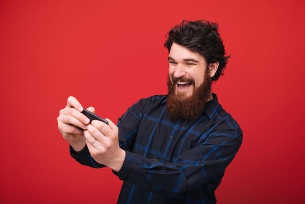 ハンサムな幸せなひげを生やした男は赤い壁の上に立って携帯電話で遊んでいます。