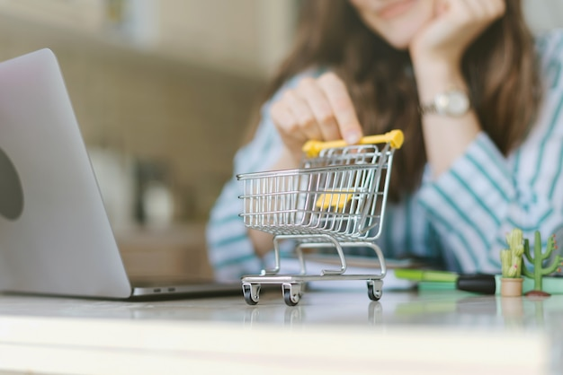 トロリーカートでオンラインショッピングをする女性の写真。