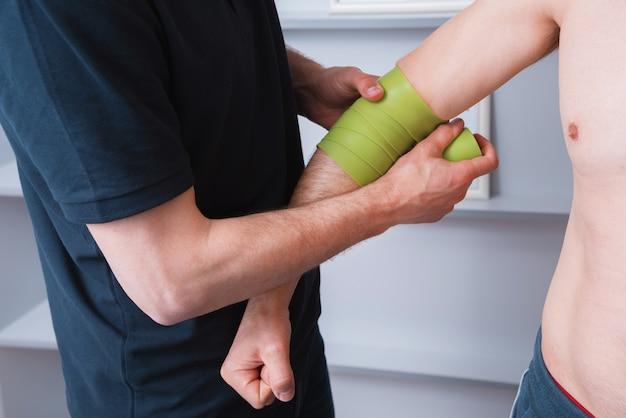 運動学テーピング。運動療法士が患者の肘に運動学テープを貼る。