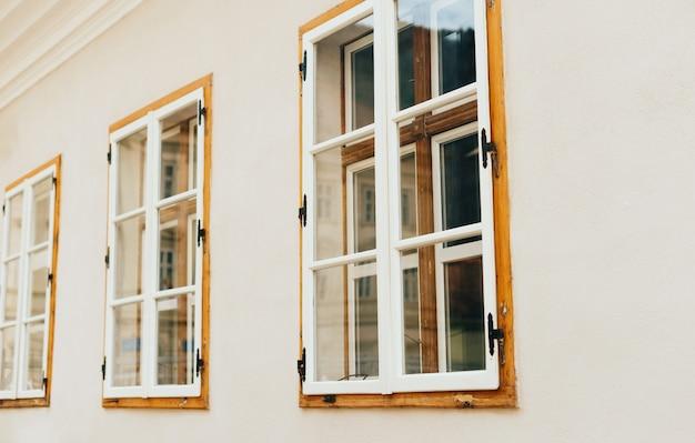 Фото деревянных окон в перспективе на белой стене.
