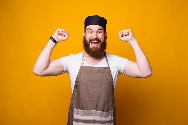 Фото веселый молодой шеф-повар празднует над