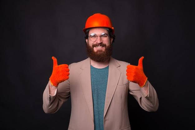 Портрет улыбающегося молодого архитектора показывает палец вверх и носить перчатки и подол
