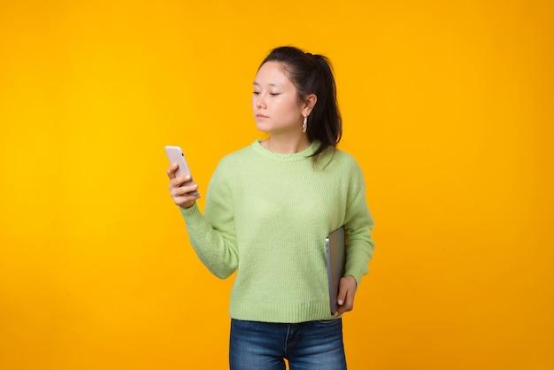 若い女性はラップトップを押しながら彼女の電話を使用しています