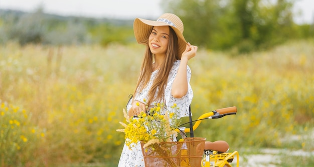 帽子をかぶっている若い女性の肖像画は夏の時間にフィールドの彼女の自転車の近くに立っています。
