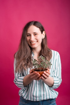 陽気な若い女性はピンクの小さな植物を保持しています。