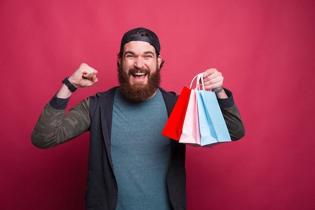 ひげを生やした勝者男はいくつかの買い物袋を保持しています。