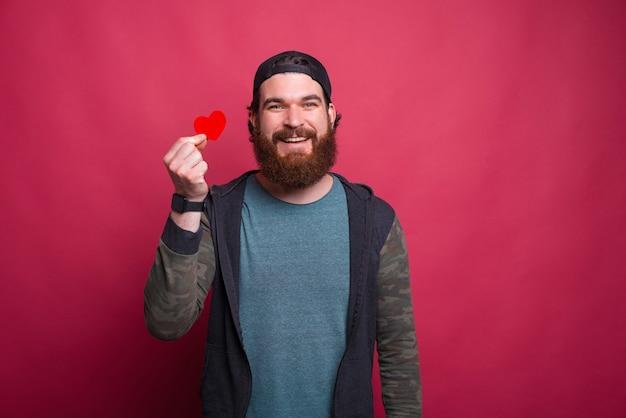 笑顔の流行に敏感な男は赤い小さな心を保持しています。