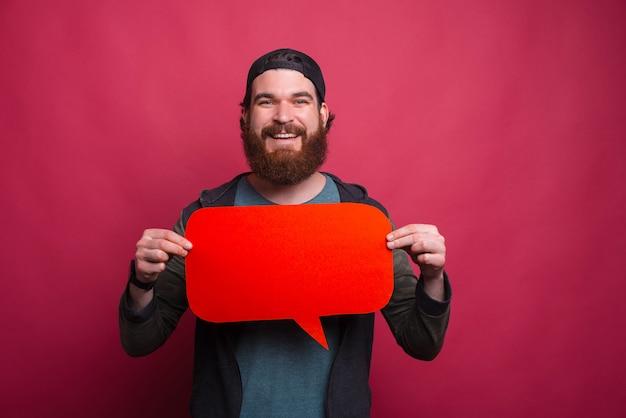 笑顔の流行に敏感な男が赤いバブルのスピーチを保持しています。